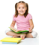 Cute little girl reads a book Stock Image