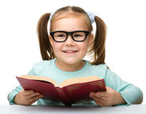 Cute little girl reads a book Stock Photos