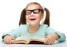 Cute little girl reads a book Royalty Free Stock Images