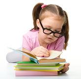 Cute little girl reads a book wearing glasses Royalty Free Stock Photos