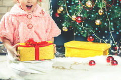 Cute little girl receive a gift near decorating Christmas tree. Royalty Free Stock Photos