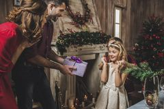 Girl receiving present. Cute little girl receiving Christmas present from her parents royalty free stock photo
