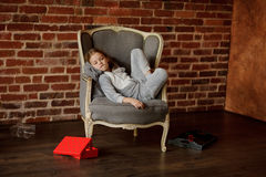 Cute little girl reclines in chair with a wistful look. Cute little girl in soft pajamas reclines in a chair with a wistful look. She has retired to the empty Royalty Free Stock Photography