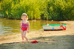 A cute little girl in a red bathing suit standing on the beach against the backdrop of boats Stock Images
