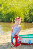 A cute little girl in a red bathing suit standing on the beach against the backdrop of boats Royalty Free Stock Image
