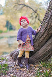 Cute little girl in a red cap near lake at the Stock Photo