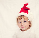 Cute little girl in red christmas hat Stock Images