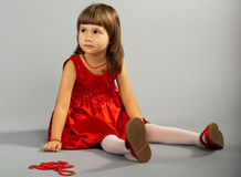 Cute little girl in a red dress Stock Images