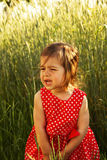 Cute little girl in red dress is crying in summer day Stock Images