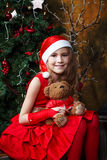 Cute little girl in a red dress near a Christmas tree. Cute little girl in a red dress holding a teddy bear near a Christmas tree Royalty Free Stock Photos