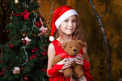 Cute little girl in a red dress near a Christmas tree. Cute little girl in a red dress holding a teddy bear near a Christmas tree Royalty Free Stock Photography
