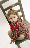 Cute little girl in red dress sitting on a chair Stock Image
