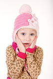 Cute little girl in red hat holding hands to face in surprise Royalty Free Stock Image