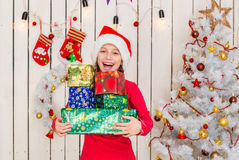 Cute little girl in red hat holding presents Royalty Free Stock Photo
