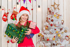 Cute little girl in red hat holding presents Royalty Free Stock Photos