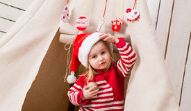 Cute little girl in red hat with toy-ball in hands near wigwam Royalty Free Stock Photos