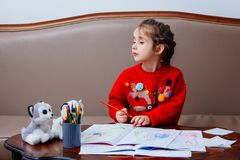 New year christmas pensil little girl writes letter Santa red jacket toy pen kid table sofa Stock Photos