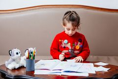New year christmas pensil little girl writes letter Santa red jacket toy pen kid table sofa Stock Photography