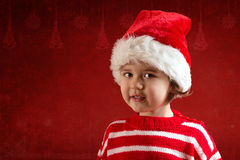 Cute little girl in red santa hat. On the red background Royalty Free Stock Photos