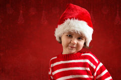 Cute little girl in red santa hat. On the red background Stock Images