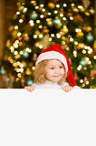 Cute little girl with red santa hat holding white board with space for text Royalty Free Stock Photo