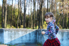 Cute little girl in red skirt runs in sunny green park Stock Photography