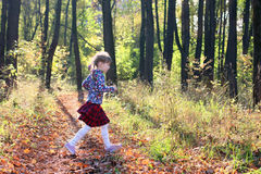 Cute little girl in red skirt runs in sunny park Stock Photo