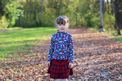 Cute little girl in red skirt stands in sunny park Stock Image