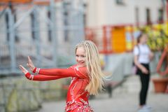 A cute little girl in a red suit is dancing on the street. Girl in the dance class. Baby girl learns dance. Show dance to the. Cute little ballerina in pink stock photos