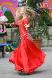 A cute little girl in a red suit is dancing on the street. Girl in the dance class. Baby girl learns dance. Show dance to the. Cute little ballerina in pink royalty free stock image