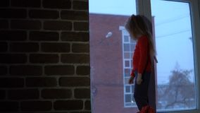 Little cute girl standing on the window sill, looking out on a snowy cityscape. A cute little girl in a red T-shirt with a long sleeve is standing on the stock footage
