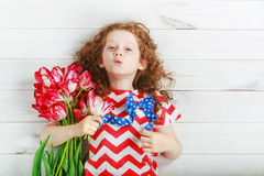 Cute little girl with red tulips on celebrating 4th july. Indepe Royalty Free Stock Images