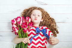 Cute little girl with red tulips and giving air kiss. Stock Photography