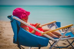 Cute little girl relax on tropical beach. Vacation stock photo