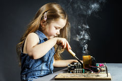 Cute little girl repair electronics by cooper-bit. Cute little girl helping father to repair old computer motherboard using solderer Stock Image