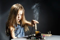 Cute little girl repair electronics by cooper-bit. Cute little girl helping father to repair old computer motherboard using solderer Royalty Free Stock Images