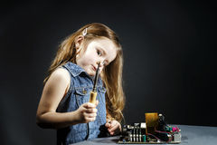 Cute little girl repair electronics by cooper-bit. Cute little girl helping father to repair old computer motherboard using solderer Stock Photos