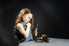 Cute little girl repair electronics by cooper-bit. Cute little girl helping father to repair old computer motherboard using solderer Royalty Free Stock Photography