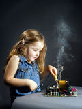 Cute little girl repair electronics by cooper-bit. Cute little girl helping father to repair old computer motherboard using solderer Royalty Free Stock Photos