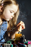 Cute little girl repair electronics by cooper-bit Stock Photo