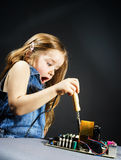 Cute little girl repair electronics by cooper-bit Royalty Free Stock Images