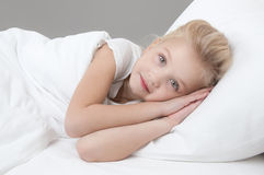 Cute little girl resting in the bed closeup. Cute little girl resting in the bed with his hands behind his head on a white pillow and looking at the camera Stock Photos