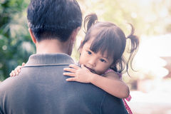 Cute little girl resting on her father's shoulder Stock Image