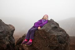 Cute little girl resting on a volcanic boulder of Mount Etna Stock Photos