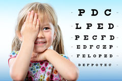 Cute little girl reviewing eyesight on chart. Royalty Free Stock Images