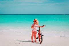 Cute little girl ride bike on beach. Cute little girl ride bike on tropical beach Stock Image