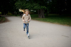 The cute little girl rides a scooter in city park. Stock Images