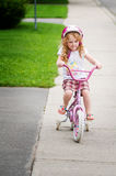 Cute little girl riding a bike. Four year old girl learns to ride a bike Royalty Free Stock Photo