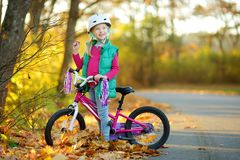 Cute little girl riding a bike in a city park on sunny autumn day. Active family leisure with kids. Child wearing safety hemet while riding a bicycle stock photo