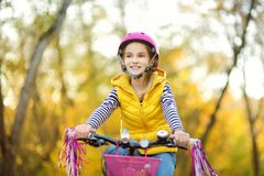Cute little girl riding a bike in a city park on sunny autumn day. Active family leisure with kids. royalty free stock photos